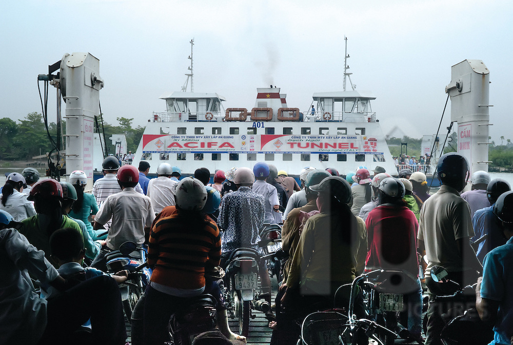Passengers in a ferry crossing the river at ben Pha Tac Cau near Rach Gia, Kien Giang province, Vietnam