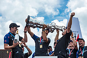The Great Sound, Bermuda, 26th June 2017. Emirates Team New Zealand helmsman Peter Burling and trimmer Blair Tuke help shore crew manager Sean Regan to drink Moet champagne from the America's Cup.