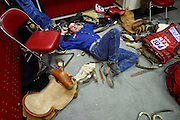 """08 DECEMBER 2002 - LAS VEGAS, NEVADA, USA: Mike Outhier, a saddle bronc rider from Utopia, TX, relaxes in the saddle bronc locker room at the Thomas and Mack Center before the third round of the National Finals Rodeo in Las Vegas, NV, Dec. 8. 2002. The NFR is the """"Super Bowl"""" of rodeo, only the top 15 cowboy from each of the Professional Rodeo Cowboy's Association are invited to participate, which runs for 10 days in Las Vegas, NV.  PHOTO BY JACK KURTZ"""