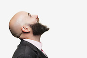 Young bald man with a beard wearing a stylish jacket, mouth open