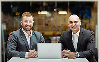 Public relations portrait featuring two businessman with laptop on table and modern blurred background