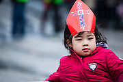 Asian child wearing Saint Nicolas Mitre at Sinterklaas parade, Dam Square, Amsterdam, 14th November 2010. Sinterklaas, the basis for Santa Claus in other countries, arrives from Spain by boat,  accompanied by Black Peter, played by multitudes of white Dutch people in blackface - a tradition that evokes some controversy. Contrary to traditions of Santa Claus elsewhere, Sinterklass arrives by boat, then rides through the streets on his grey horse, Amerigo,  in mid-November, bringing in the Christmas season. The Zwarte Pieten (Black Peters) distribute sweets and gingerbread cookies to the crowd along the parade route.