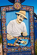 Tombstone showing a man painting the tombstones,  The  Merry Cemetery ( Cimitirul Vesel ),  Săpânţa, Maramares, Northern Transylvania, Romania.  The naive folk art style of the tombstones created by woodcarver  Stan Ioan Pătraş (1909 - 1977) who created in his lifetime over 700 colourfully painted wooden tombstones with small relief portrait carvings of the deceased or with scenes depicting them at work or play or surprisingly showing the violent accident that killed them. Each tombstone has an inscription about the person, sometimes a light hearted  limerick in Romanian. .<br /> <br /> Visit our ROMANIA HISTORIC PLACXES PHOTO COLLECTIONS for more photos to download or buy as wall art prints https://funkystock.photoshelter.com/gallery-collection/Pictures-Images-of-Romania-Photos-of-Romanian-Historic-Landmark-Sites/C00001TITiQwAdS8