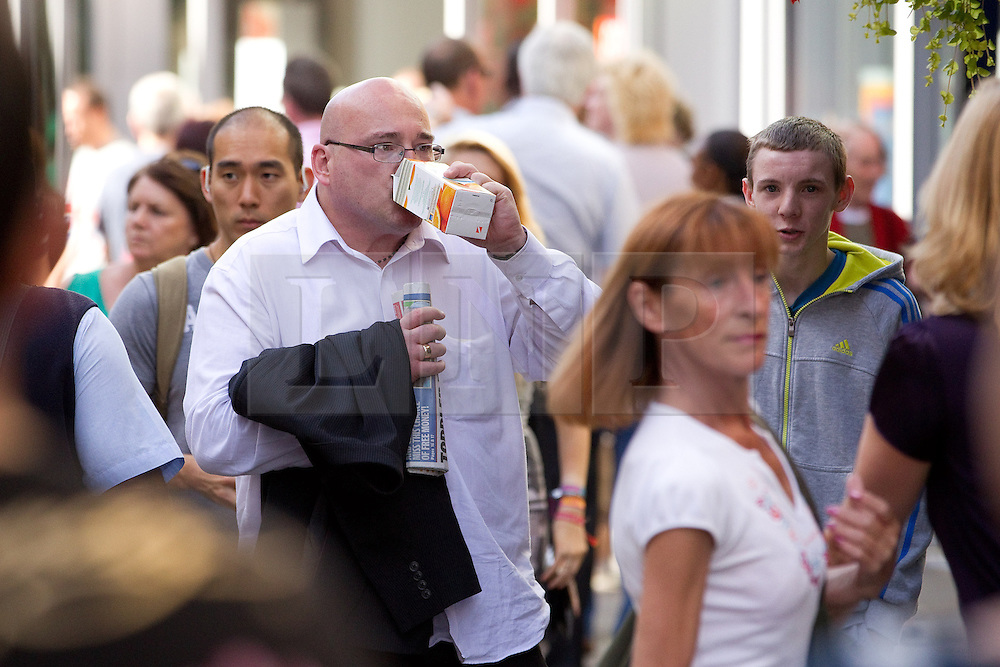 © Licensed to London News Pictures .  08/09/2012 . Manchester, UK . Domenyk Noonan (in white shirt and glasses in centre) , recently released from prison , walks along Manchester 's Market Street . The area was the scene of looting and rioting on 9th August 2011 , during which Noonan was arrested . Noonan has announced he plans to sue the police over the  arrest . Under the terms of a previous early release , the arrest lead to him being recalled to prison . Photo credit : Joel Goodman/LNP