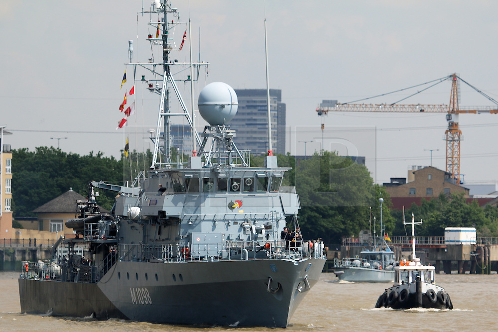 © Licensed to London News Pictures. 15/05/2014. Workers at Canary Wharf were surprised to see a flotilla of Germany Navy vessels appear outside their offices today. The port visit to London by the German Navy includes two mine sweepers (Siegburg and Auerbach), four remotely controlled drone ships, a refueling ship and more. The vessels will remain at West India Dock for the weekend. Minesweeper mothership pictures with drone behind. Credit : Rob Powell/LNP