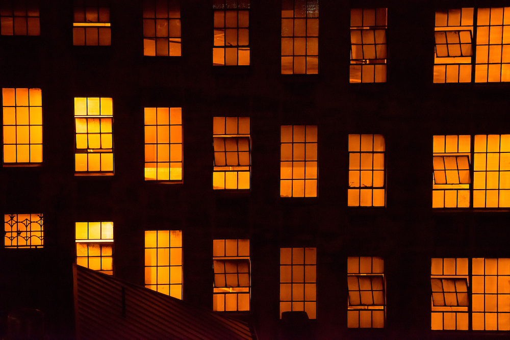 Golden glow of incandescent lighting illuminates an industrial building through the grid of windows at night