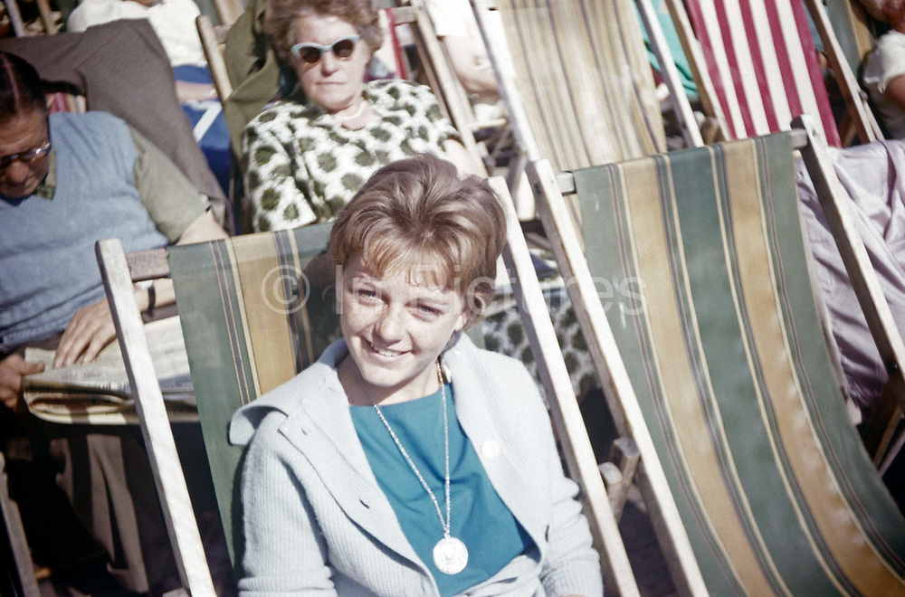 A teenage girl smiles in summer sunshine while sitting on a seafront deckchair in the early nineteen sixties. It is the beginning of a new decade and an exciting time for a English teenage girl. She smiles at her father taking the photo for the family album while a more suspicious woman in the background wears classic sunglasses.