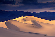 Storm clouds over star sand dunes and mountains at sunset, Stovepipe Wells, Death Valley National Park, California