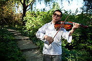 Man playing the violin in Zizhuyuan Park in Beijing, China. This park is well known as a place where middle aged or elderly Chinese come. This can take all forms including some surprising ones. Purple Bamboo Park (Zi Zhu Yuan Gongyuan) also called Zizhuyuan Park or Black Bamboo Park largest parks in Beijing. It is located in the Haidian District. The park consist of three connecting lakes covering over a total area of 48 hectares. Typical of the classical Chinese garden style, and like many of Beijing's parks and gardens, it is a mountain-water landscaped garden. Constructed around canals and large lakes, the Bamboo Park is known for its liberal use of verdant bamboo groves. The garden has a variety of bamboos on display. Young people also believe that if they go to the park as a couple that their relationship is doomed to fail.