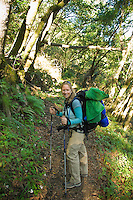 A backpacker stops for a rest on Pine Ridge Trail, Big Sur, California.
