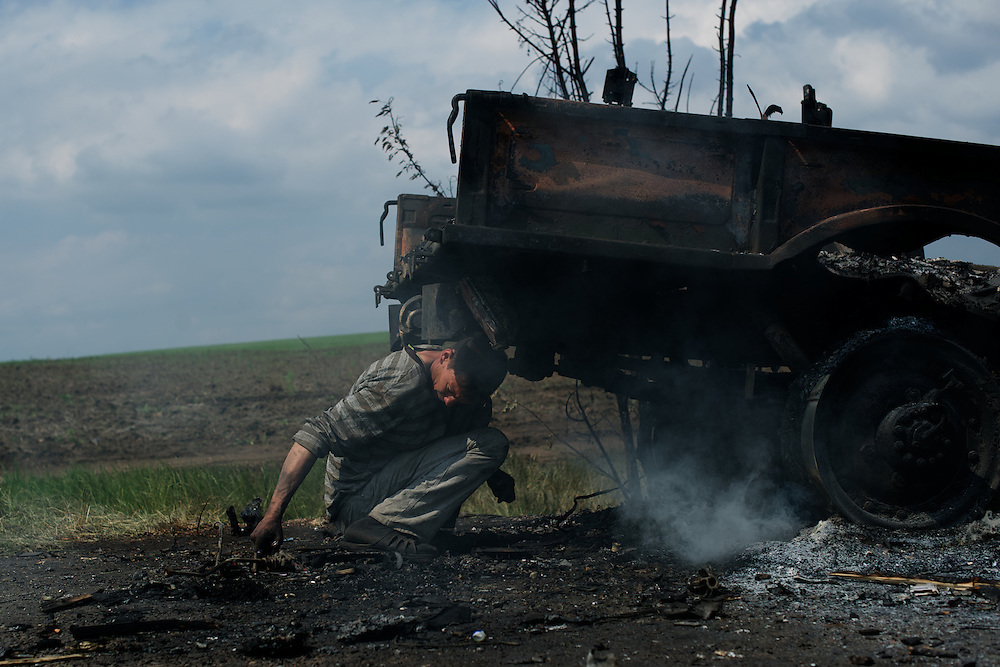 A man salvages scrap metal from a destroyed truck in Oktyabrskaya, eastern Ukraine. Pro-Russian militants ambushed Ukrainian troops nearby the day before, killing seven and wounding another eight in the most deadly attack yet on Ukrainian forces.