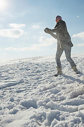 Woman throwing snowball, Bavaria, Germany