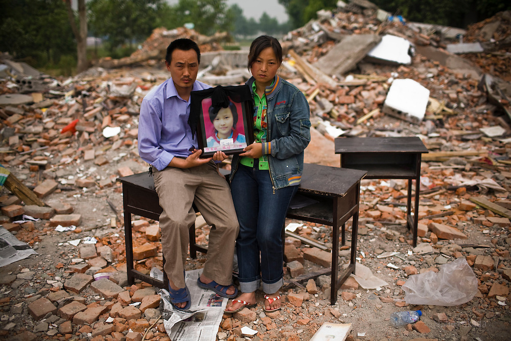 Zhang Fa Ming, 37, left, and Zhao Zheng Yin, 35, holding a picture of daughter Zhang Yi, 12,  are seen  at Fuxin No.2 Primary  School in Wufu, Sichuan province.