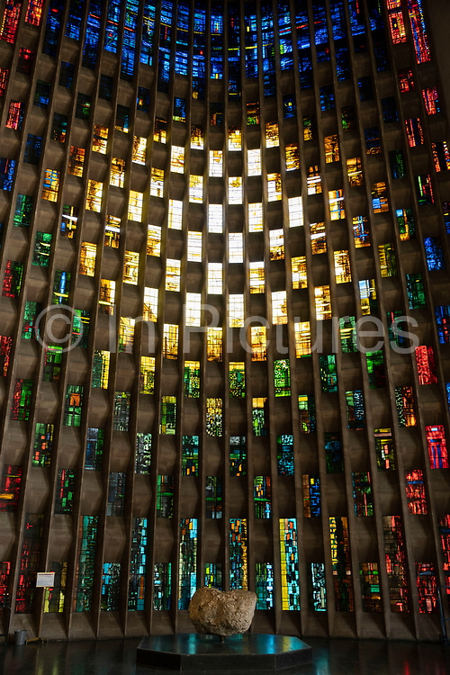 The baptistry window designed by John Piper and made by Patrick Reyntiens inside Coventry Cathedral also known as St Michael's, a modern cathedral founded in 1956 and well known for having stunning modernist stained glass, minimalist structure and large scale tapestry on 23rd June 2021 in Coventry, United Kingdom. The Cathedral Church of Saint Michael, commonly known as Coventry Cathedral, is the seat of the Bishop of Coventry and the Diocese of Coventry within the Church of England. The current St Michael's Cathedral, built next to the remains of the old, was designed by Basil Spence and Arup, built by John Laing and is a Grade I listed building.