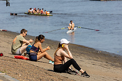 Licensed to London News Pictures. 17/07/2021. London, UK. Sunbathers enjoy the hot sunshine along the River Thames at Putney Embankment, southwest, London today as weather forecasters predict a very warm and dry Weekend with highs of over 32c in London and the south East with the warm weather lasting up to two weeks. Photo credit: Alex Lentati/LNP