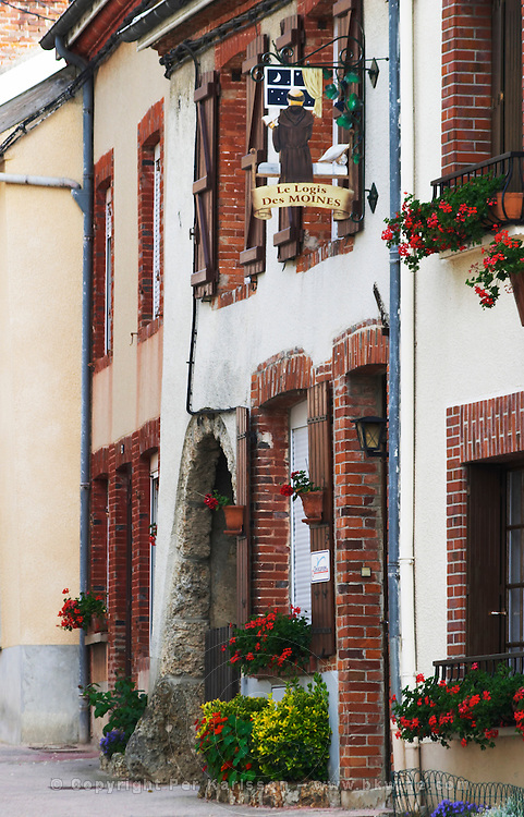 A wrought iron painted sign that illustrates the theme of champagne and wine production: showing a monk looking out of a window and a village hose on a street decorated with many colourful flowers, the village of Hautvillers in Vallee de la Marne, Champagne, Marne, Ardennes, France