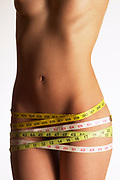 Side lit photo of woman's torso with measuring tape wrapped around hips many times