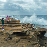 Pacific Ocean waves crash ashore as a couple has wedding photos taken on  on the southeast shore of Oahu, Hawaii.
