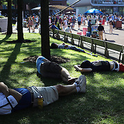 Spectators relax in the sunshine outside Arthur Ashe Stadium during the US Open Tennis Tournament, Flushing, New York. USA. 29th August 2012. Photo Tim Clayton