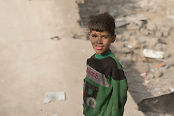 Licensed to London News Pictures. 08/11/2016. Qayyarah, Iraq. An oil covered young Iraqi boy is seen in a destroyed ISIS headquarters, located in a football stadium destroyed by an airstrike, where he and his friends are playing in the Iraqi town of Qayyarah, Iraq. Oil wells in and around the town of Qayyarah, Iraq, we set alight in July 2016 by Islamic State extremists as the Iraqi military began an offensive to liberated the town.<br /> <br /> For two months the residents of the town have lived under an almost constant smoke cloud, the only respite coming when the wind changes. Those in the town, despite having been freed from ISIS occupation, now live with little power, a water supply tainted with oil that only comes on periodically and an oppressive cloud of smoke that coats everything with thick soot. Many complain of respiratory problems, but the long term health implications for the men, women and children living in the town have yet to be seen. Photo credit: Matt Cetti-Roberts/LNP