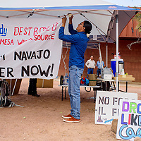 Adrian Herder ties up a banner protesting Peabody Energy outside the Navajo Department of Education in Window Rock Monday.