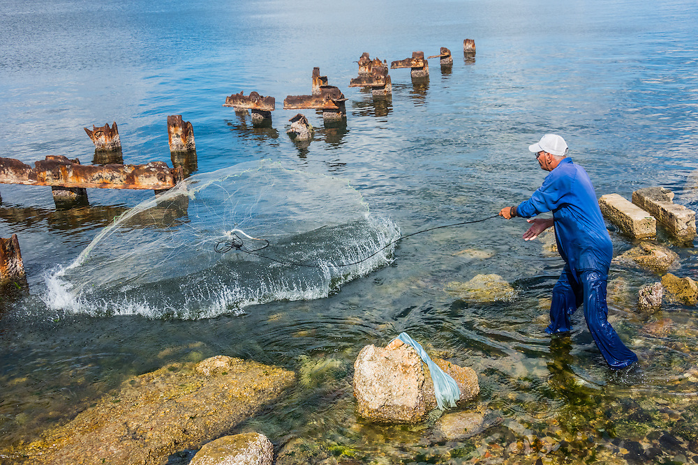 A man throws a fishing net in Regla, Havana, Cuba.