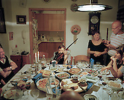 A former member of the Palmach, a pre-Israel defense force holds her rifle at the dinner table while her family celebrates Israeli Independence Day at their home.