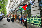 """London, United Kingdom, May 28, 2021: People holding banner, placards and waving Palestinian flags are shouting """"Shut Elbit Down"""" outside HQ Office of Elbit Systems in central London on Friday, May 28, 2021. Elbit is an Israel-based international defence electronics company engaged in a wide range of weapons programs throughout the world. (Photo by Vudi Xhymshiti)"""