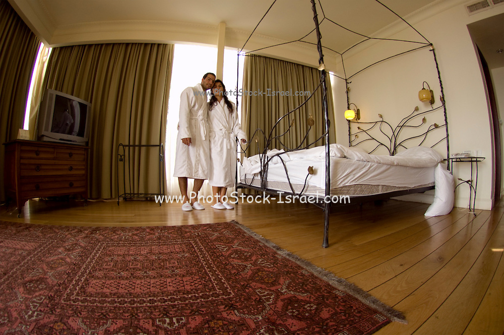 Honeymoon couple dressed in bathrobes in a hotel suite full body view