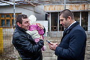 Local inhabitants meeting in front of the polling station in Marginenii de Jos. Right non Roma mayor Manole Aureliantalking to a local inhabitants holding his child.
