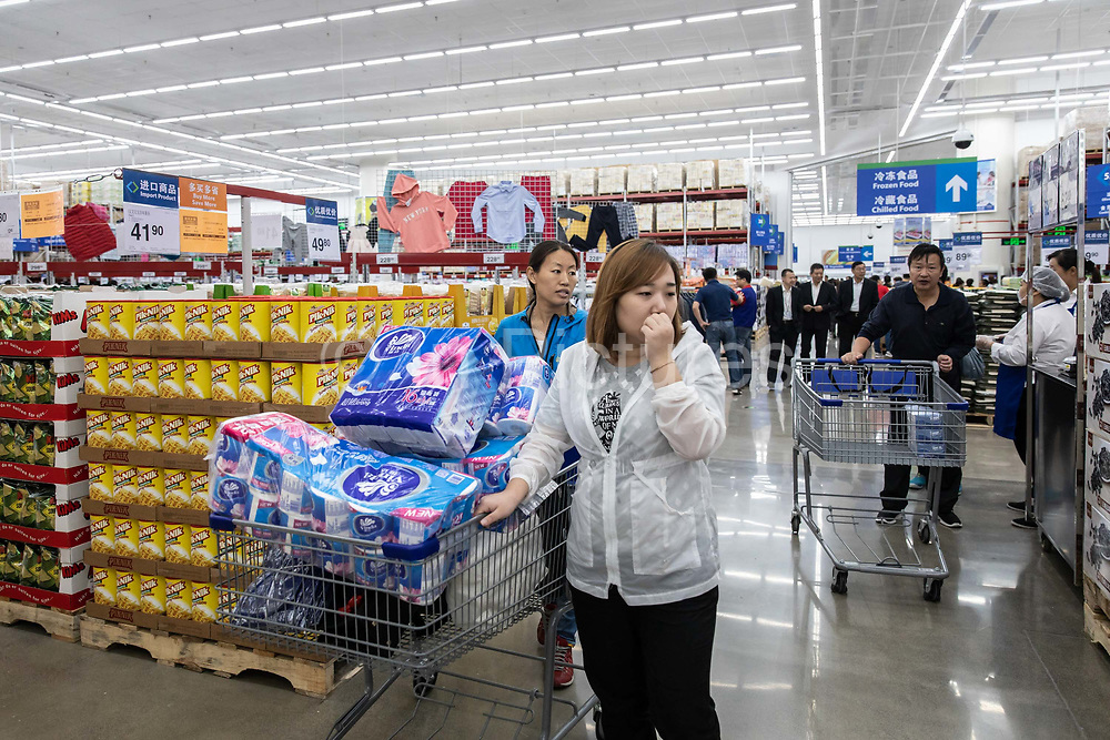 Customers shop in a Wal-Mart Stores Inc. owned and operated Sams Club store during its opening day in Tianjin, China, on Wednesday, Sept. 28, 2016.