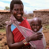 Africa, Kenya, Maasai Mara. A young mother and her baby at Olanana in the Maasai Mara.