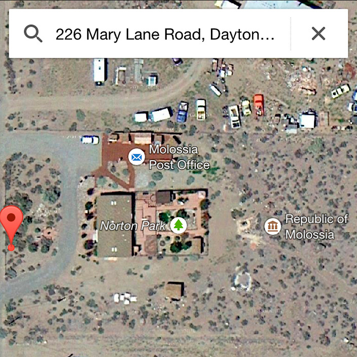 """If you deiced to make the trip out, 1.) make sure he knows you're coming and 2.) maybe don't use Apple Maps. It brought me to one of their neighbor's houses. This is the Google Maps satellite view of The Republic of Molossia. Some might call it, the poor man's aerial photograph. The micronation is surrounded by the Baugh's neighbors -- all U.S. citizens I assume -- and the small desert town of Dayton, Nevada. It's a little less than an hour drive from Reno or, as molossia.org advises in the Klonitz measurement system, it's """"over forty-eight Imperial Nortons ( 48 km / 30 mi) from the nearest airport and eleven Imperial Nortons (11 km / 7 mi) from the nearest hotel accommodations and restaurants."""" I wouldn't say Molossia is in the middle of nowhere -- I totally stopped for some Starbucks off Route 40 -- but nowhere is right around the corner."""