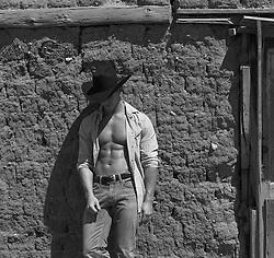 cowboy with an open shirt against an adobe wall