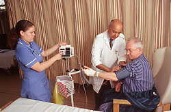 Male doctor and female nurse measuring elderly man's blood pressure,