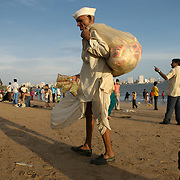 An old man selling popcorn attempts to initiate eye contact with potential customers at Chowpatti beach, Mumbai, June 2007