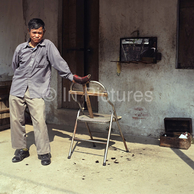 Portrait of a hairdresser/barber in Thuy Ung village, Ha Tay province, Vietnam.