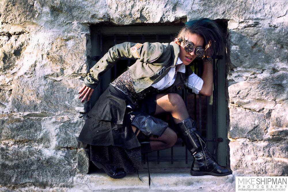 Steampunk girl posing in stone window wearing goggles