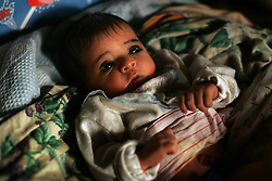 A Bedouin baby, who has yet to be named, has his arms and legs tightly bound, by his mother Nofa Ali Odah Rashaida, in preparation for visitors, Bethlehem, Palestinian Territories, Nov. 16, 2004. The binding is done to keep the baby's arms and legs straight after being bent in the fetal position for so long while in the womb. Bedouins also believe it enables babies to sleep easier. Rashaida's eighth child was born in a small village outside of Bethlehem on the day of Yasser Arafat's death.
