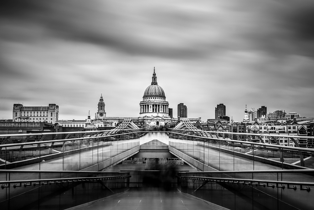 Long exposure monochrome image of the Millenium Bridge with blurred pedestrians and St Pauls Cathedral in thew background