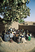 """The Imam of Kouakourou village on the banks of the Niger River in Mali,  teaches a Koranic lesson to students. Several of Soumana Natomo's children attend these classes, along with classes at what they call, """"the modern school"""" taught in French where they learn math and reading. The Natomo family lives in two mud brick houses in the village of Kouakourou, Mali, on the banks of the Niger River. They are grain traders and own a mango orchard. According to tradition Soumana is allowed to take up to four wives; he has two. Wives Pama and Fatoumata are partners in the family and care for their many children together. Material World Project."""