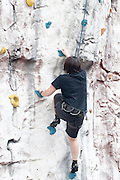 Young teen girl climbs up an artificial climbing wall Model release available