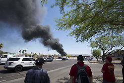 April 27, 2018 - Phoenix, Arizona, U.S - Pedestrians watch as firefighters work the scene of a fire at a recycling plant near 13th Avenue and Harrison Street in Phoenix, Arizona, on Friday, April 27, 2018. (Credit Image: © Ben Moffat/via ZUMA Wire via ZUMA Wire)