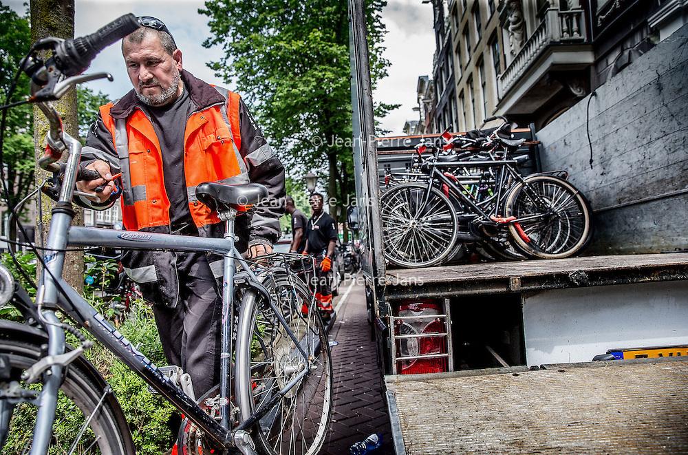 """Nederland, Amsterdam, 24 juni 2016.<br />Elke maand organiseerde het Fietsdepot voor professionele opkopers een veiling van de fietsen die niet binnen zes weken zijn opgehaald door hun eigenaar. Maandagochtend vindt voor de laatste keer een fietsveiling plaats. Voor die speciale gelegenheid neemt wethouder Pieter Litjens (Verkeer) de veilinghamer ter hand.<br />Vanaf 1 juli is het Haarlemse bedrijf TradeFRM verantwoordelijk voor de verkoop van niet-opgehaalde fietsen aan handelaren en aan socialewerkprojecten. """"Ook het niet verkoopbare materiaal zal door TradeFRM op de meest duurzame manier worden gerecycled en hergebruikt,"""" aldus de gemeente.<br />Alle door de gemeente weggeknipte fietsen komen terecht op het terrein van het Fietsdepot in het Westelijk Havengebied. Amsterdammers kunnen daar terecht om hun weggeknipte fiets weer op te halen. Dat kost sinds 1 januari dit jaar 22,50 euro. Daarvoor was dat 15 euro. Thuis laten bezorgen kan ook, voor 50 euro. Iets minder dan de helft van de fietsen worden door de eigenaar opgehaald.<br />Op de foto: Fietsen die te lang langs de grachten blijven staan worden door de Gemeente weggesleept.<br /><br /><br />Foto: Jean-Pierre Jans"""