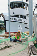 A woman mends gillnet at the harbor dock in Haines, Alaska during the salmon season.