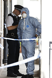© Licensed to London News Pictures. 01/07/2020. London, UK. A police forensics officer works outside a block of flats in Monarch Parade in Mitcham, south London where a four year old girl was found seriously injured yesterday. She was taken to hospital where she later died. A woman, aged 35, is fighting for her life after she was also found suffering serious injuries inside the property. Photo credit: Peter Macdiarmid/LNP