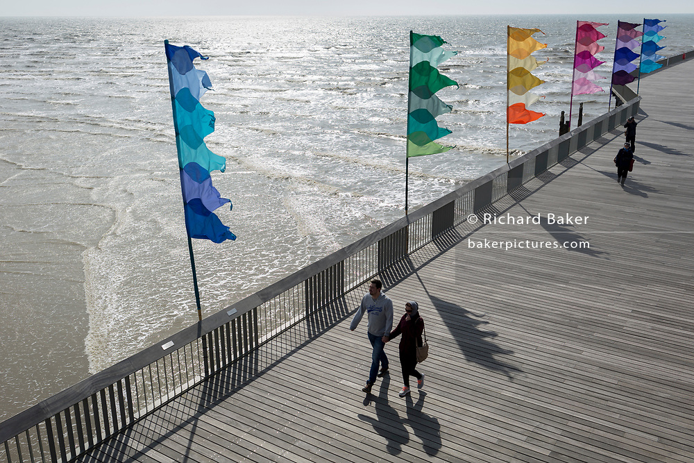 Visitors to Hastings Pier walk beneath Bank Holiday flags, on 29th April 2017, at Hastings, East Sussex, England.