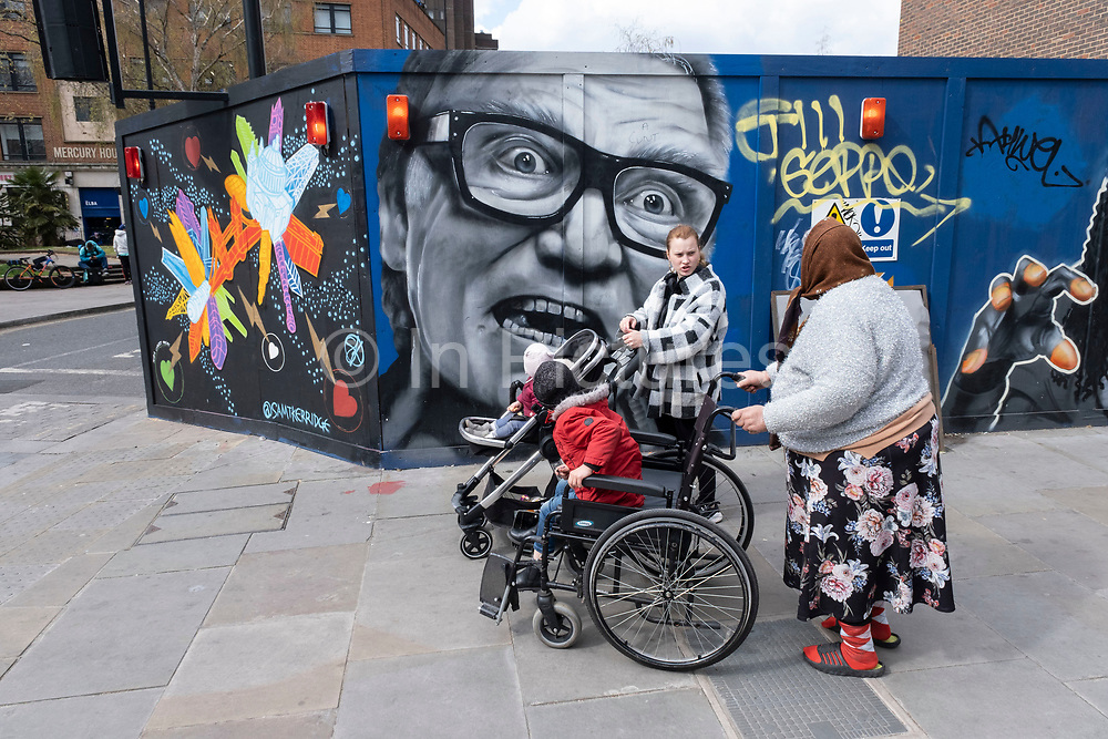 People passing a hoarding covered in street art of the character Brick Top from the crime film Snatch by Guy Ritchie and starring the actor Alan Ford, on a site in Waterloo on 13th April 2021 in London, United Kingdom. The character was known for his fearsome dialogue as the crime villain.