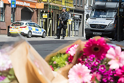 London, June 4th 2017. Flowers are left by well-wishers as a policeman stands guard on Borough High Street during a massive policing operation in the aftermath of the terror attack on London Bridge and Borough Market on the night of June 3rd which left seven people dead and dozens injured