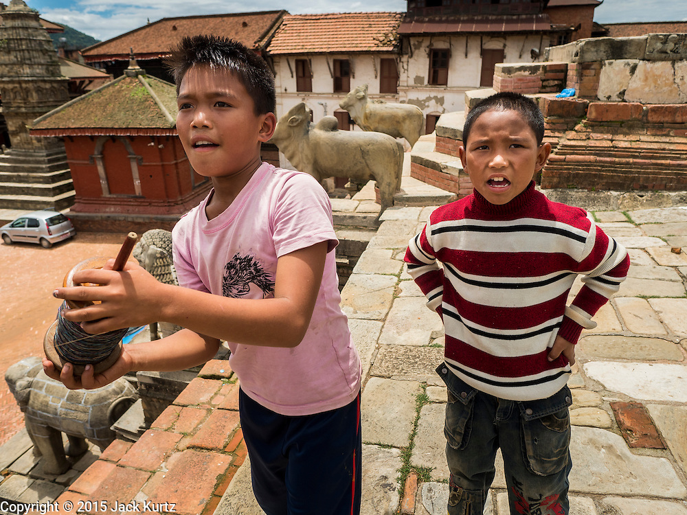 02 AUGUST 2015 - BHAKTAPUR, NEPAL:  Boys fly their kite from the top of a temple destroyed by the Nepal earthquake. The Nepal Earthquake on April 25, 2015, (also known as the Gorkha earthquake) killed more than 9,000 people and injured more than 23,000. It had a magnitude of 7.8. The epicenter was east of the district of Lamjung, and its hypocenter was at a depth of approximately 15km (9.3mi). It was the worst natural disaster to strike Nepal since the 1934 Nepal–Bihar earthquake. The earthquake triggered an avalanche on Mount Everest, killing at least 19. The earthquake also set off an avalanche in the Langtang valley, where 250 people were reported missing. Hundreds of thousands of people were made homeless with entire villages flattened across many districts of the country. Centuries-old buildings were destroyed at UNESCO World Heritage sites in the Kathmandu Valley, including some at the Kathmandu Durbar Square, the Patan Durbar Squar, the Bhaktapur Durbar Square, the Changu Narayan Temple and the Swayambhunath Stupa. Geophysicists and other experts had warned for decades that Nepal was vulnerable to a deadly earthquake, particularly because of its geology, urbanization, and architecture.      PHOTO BY JACK KURTZ